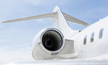 private: Jet Engine with a tail and part of a wing on a luxury private Jet Plane - Bombardier Global Express