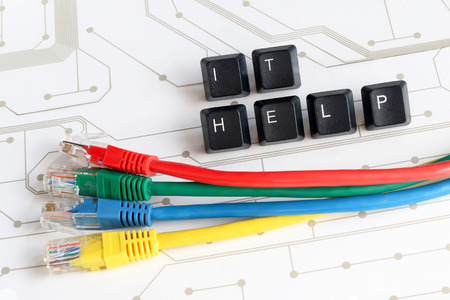 IT HELP, Assistance - Word IT HELP made of keyboard keys with colourful network cables on white circuit board background Stockfoto