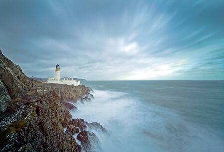 岩の崖の上に灯台と嵐の海の長時間露光。場所、ダグラス、マン島、イギリス
