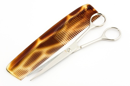 Comb and scissors on a white background