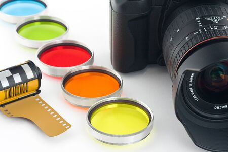 Camera, photographic film and filter on a white background Stock Photo