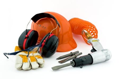seguridad e higiene: Neumático cincel, sombrero de color naranja fuerte, protección para los oídos, guantes de trabajo y gafas de seguridad en el fondo blanco Foto de archivo