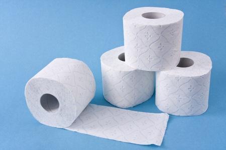 papel higienico: Cuatro rollos de papel higiénico tres de ellos para construir una pirámide se muestra en fondo azul claro. Foto de archivo