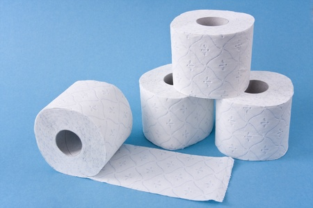 Four toilet paper rolls three of them to build a pyramid shown on light blue background. photo