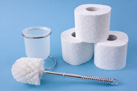 Three toilet paper rolls up into a pyramid and a toilet brush lying on a light blue background. photo
