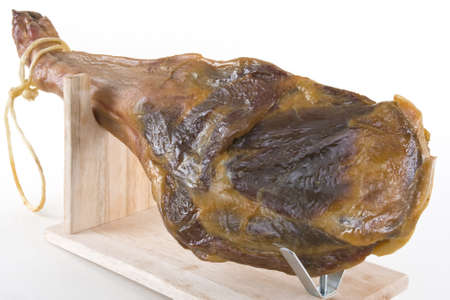 A front leg Serrano ham on mapped on a wooden stand on a white background.