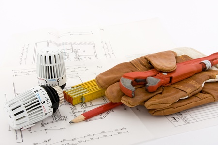 Two thermostats for a new heating are combined with a ruler, a pencil, a pipe wrench and a pair of work gloves on a blueprint.