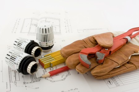 Three thermostats for a new heating are combined with a ruler, a pencil, a pipe wrench and a pair of work gloves on a blueprint. Stock Photo
