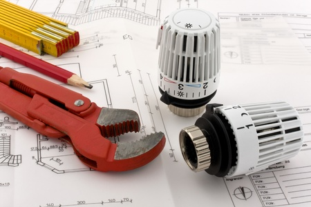 Two thermostats for a new heating are combined with a ruler, a pencil and a pipe wrench on a blueprint. Stock Photo