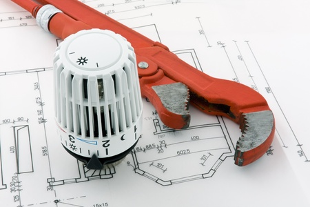 new construction renovation: A thermostat for a new heating system is combined with a pipe wrench on a blueprint.