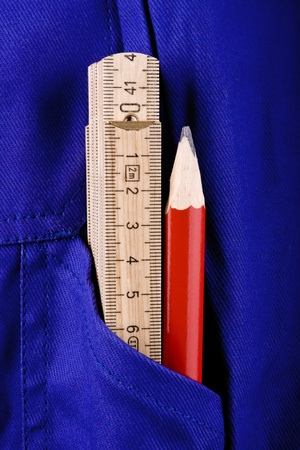 bluey: A ruler and a red pencil in the pocket of a blue work pants.