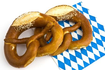 Two pretzels with salt on a Bavarian napkin on a white background into. Stock Photo