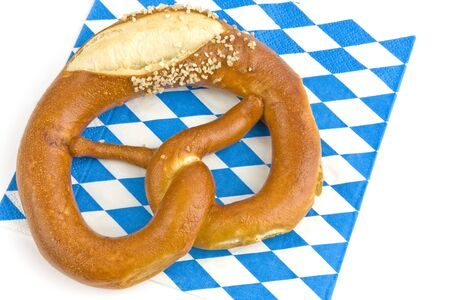 Pretzel with salt on a Bavarian napkin on a white background into.