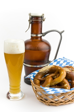 A basket of pretzels and a beer jug with a glass of wheat beer on a white background into.