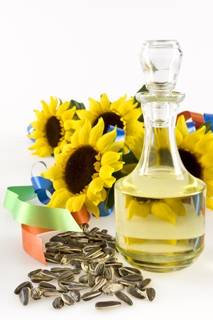 Sunflower seeds, a bottle of sunflower oil and sunflower with two colored ribbons on a white background into.