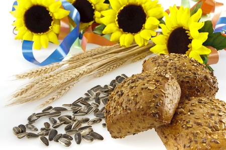 Three whole-grain bread, sunflower seeds, wheat ears, sunflowers  and colored ribbons on a white background. Stock Photo