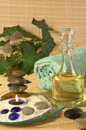 A bottle of massage oil, scented candle burning a, a bath towel and stones