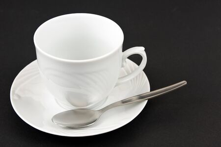 A white coffee cup with a saucer and spoon on a black background free