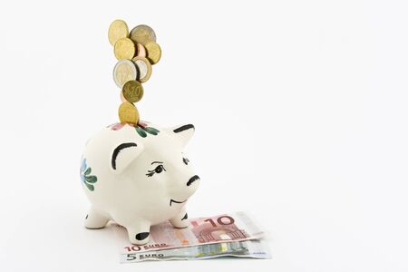 Coins falling into a piggy bank, which is depicted on banknotes on a white background. Stock Photo