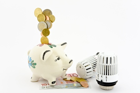 Coins falling into a piggy bank that is located on bank notes, coins and mapped where two heating thermostats on a white background.