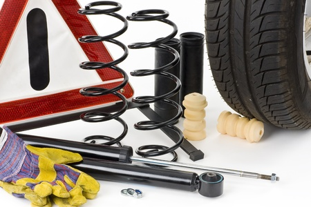 damping: Warning triangle, car tires, shock absorbers, coil springs, dampers, work gloves  and stop collars on a white background into.