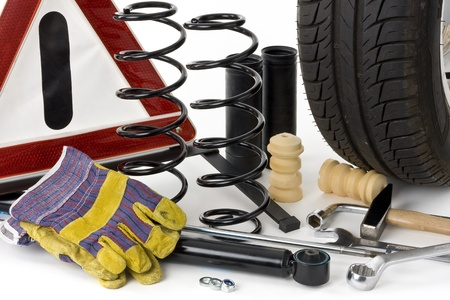 Warning triangle, car tires, shock absorbers, coil springs, dampers, work gloves, stop collars and tools on a white background into. Stock Photo