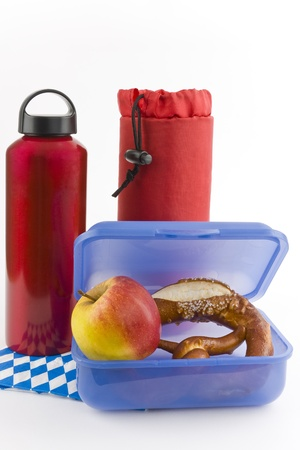 insulated drink container: A water bottle and a box with an apple and a pretzel is shown on a white background. Stock Photo