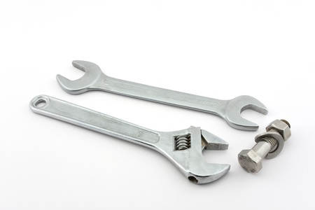 Wrench, adjustable wrench and a screw with a nut on a white background shown.