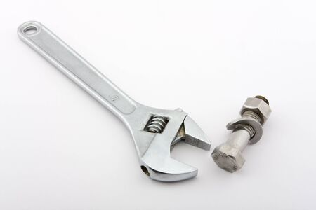 solves: An Adjustable wrench and a screw with a nut on a white background shown. Stock Photo