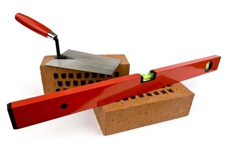 materiales de construccion: Los ladrillos, el nivel y llana sobre un fondo blanco se muestra.