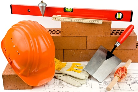 Red bricks, the hand tools of a mason, hard hat and work gloves shown on a blueprint.