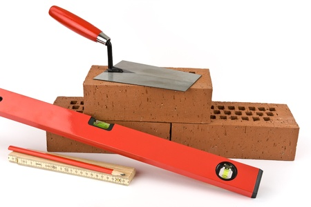 Three bricks, a spirit level, a ruler, a pencil and a trowel depicted on a white background. photo
