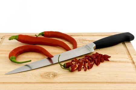 Chili peppers and a kitchen knife lying on a chopping board  Stock Photo