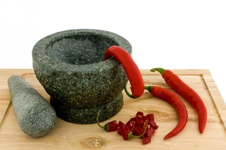 chiles picantes: Un mortero y pepperoni proyecta sobre una tabla de cortar