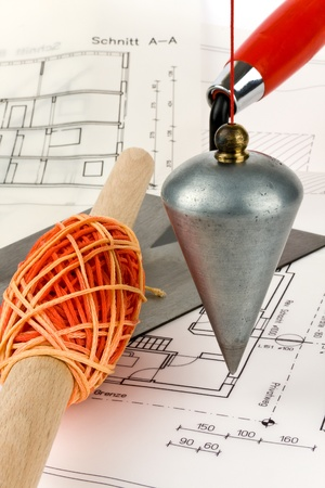 depends: A lot depends on a blueprint on which a trowel and a masons line is. Stock Photo