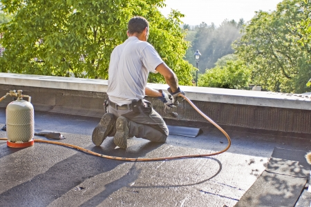 roofer: A roofer with a gas burner is kneeling on a roof, and heated a piece of roofing felt  Stock Photo