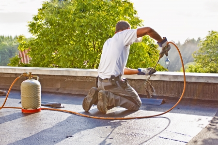 A roofer with a gas burner is kneeling on a roof, and heated a piece of roofing felt  Stock Photo