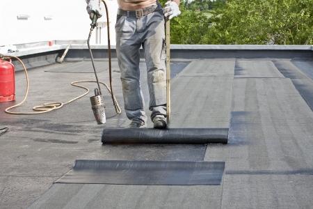A roofer coprire un tetto con cartone catramato