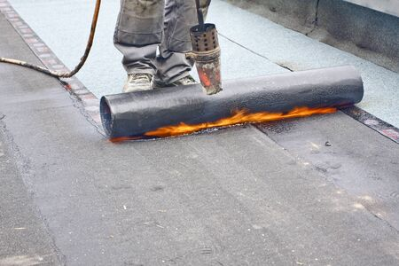 roofing felt: A roofer covering a roof with roofing felt