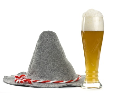 A hat and a glass of wheat beer on a white background shown.