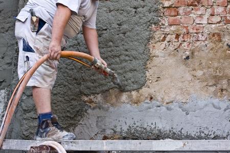 plasterer: Plasterer plastered an old exterior wall. Stock Photo