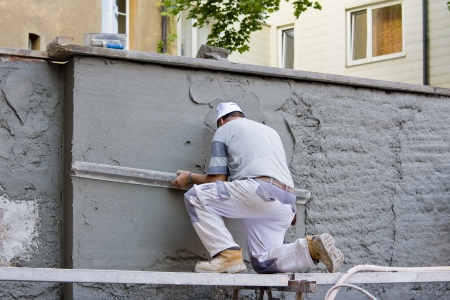 Plasterer plastered an old exterior wall. Stock Photo