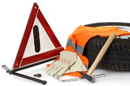 shown: Warning triangle, car tires, work gloves and tools for a flat tire on white background shown.