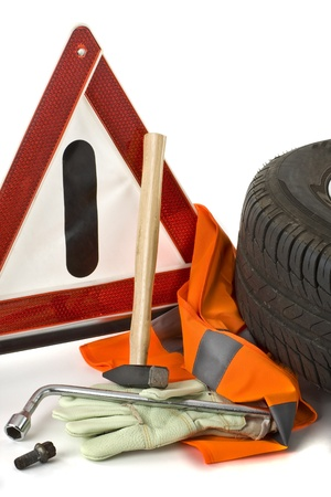 flat tire: Warning triangle, car tires, work gloves and tools for a flat tire on white background shown.