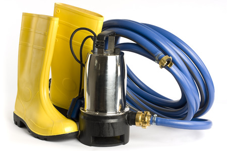 Submersible pump, rubber boots and water hose pictured on a white background