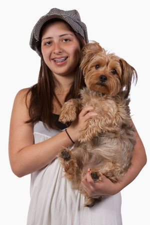 Cute young teenage Hispanic girl with braces wearing a hat holding onto pet Yorkshire Terrier dog photo