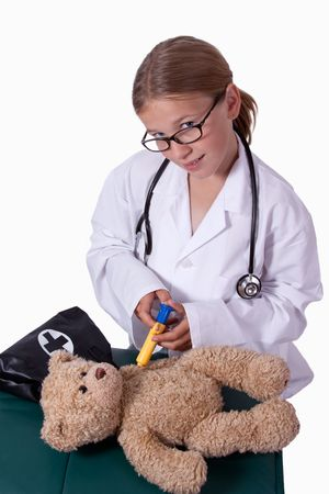 Cute little blond girl dressed up like a doctor holding a pretend needle and a brown teddy bear smiling  photo