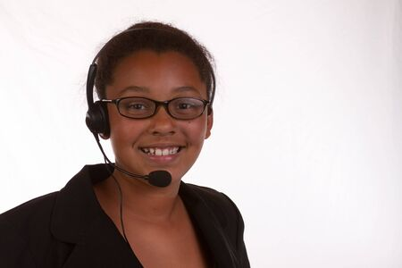 Head and shoulders of a young African American business woman wearing headset over white photo