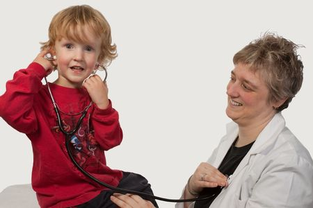 Young caucasian boy and a short hair woman in uniform holding a stethoscope on his ear listening to doctor heart beat photo