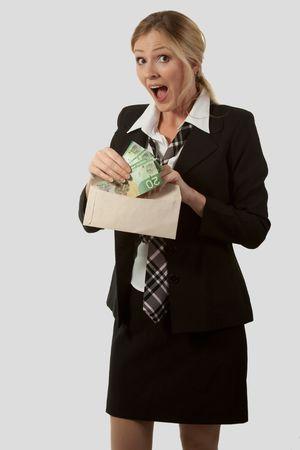 lazo regalo: Atractivo caucasian mujer rubia que llevaba un traje negro con corbata de la celebraci�n de un sobre abierto y sacar dinero de Canad� con una expresi�n de sorpresa